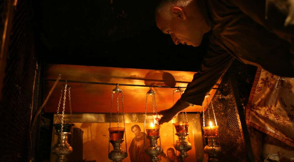 A man lights special oil lamps for Christmas by an altar showing the nativity scene at the Grotto, believed ...