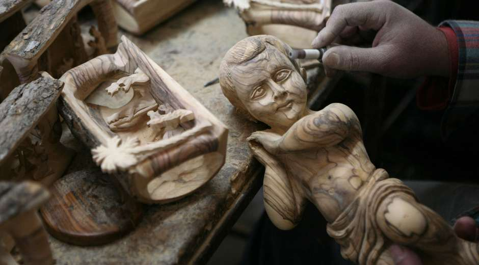 A Palestinian worker at the Giacaman Olive Wood factory makes wooden effigies of baby Jesus, on December 22, ...