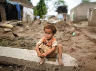 A child sits amid the ruins of his family's house in the flood ravaged town of Adiel Khan on the outskirts of Peshawar in Pakistan's northwest Khyber-Pakhtunkhwa Province August 19, 2010. More than four million Pakistanis have been made homeless by nearly three weeks of floods, the United Nations said on Thursday, making the critical task of securing greater amounts of aid more urgent. REUTERS/Tim Wimborne (PAKISTAN - Tags: DISASTER HEALTH)
