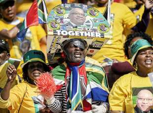 Supporters of South Africa's ruling African National Congress wearing shirts with the picture of ...