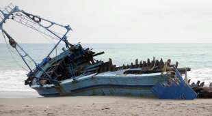 The wrecked hulk of a boat in which six illegal immigrants died lies on the beach near the Calabrian town of ...