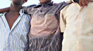 Three underage mililtia soldiers who allegedly defected from the Hizbul-Islam armed group pose for the press ...