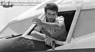 One of the hijackers of TWA Boeing 727 holding a gun, emerging from the plane cockpit window 19 June 1985 at ...