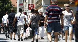 People walk down a shopping street in Munich, June 28, 2011. Contrasting fortunes tell the story of two ...