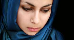 A portrait of a young arab woman in a blue