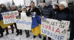 """Protesters hold posters, one in Ukrainian reading """"Putin and Assad are killers of children"""", during ..."""
