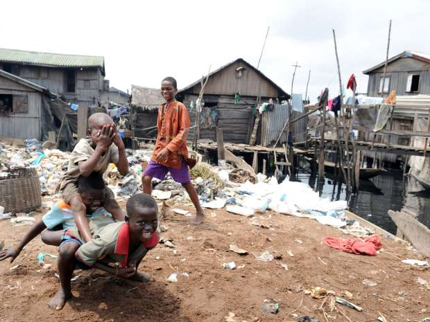 TO GO WITH STORY BY M.J. SMITH Children play next to waste in the Makoko slum in Lagos, on September 29, ...