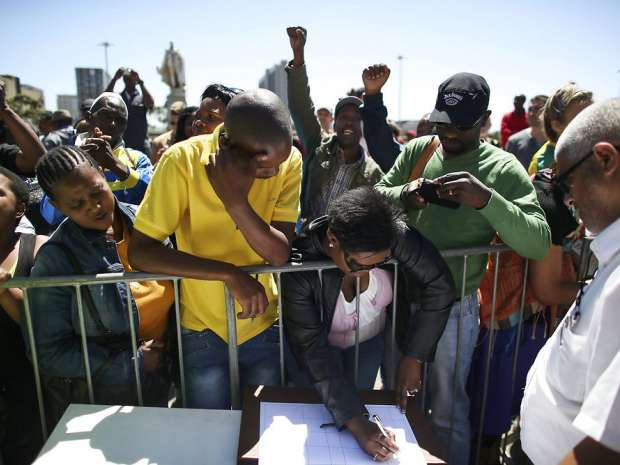 epa03979050 South African mourners sing and dance before signing a message book infront of the Cape Town City ...