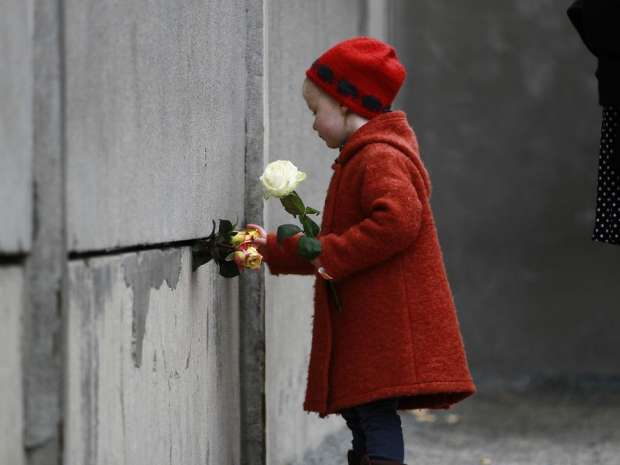 09 Nov 2014, Berlin, Germany - - - Berlin, Germany. 9th November 2014 - - A young girl places a rose in the ...
