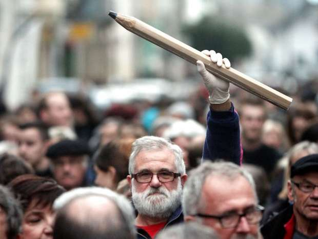 TOPSHOTS A man holds up a giant pencil during a gathering in Tarbes, southern France, on January 8, 2015, in ...