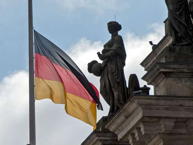 epa04708193 A German flag waves at half mast at the Reichstag building hosting the German ...