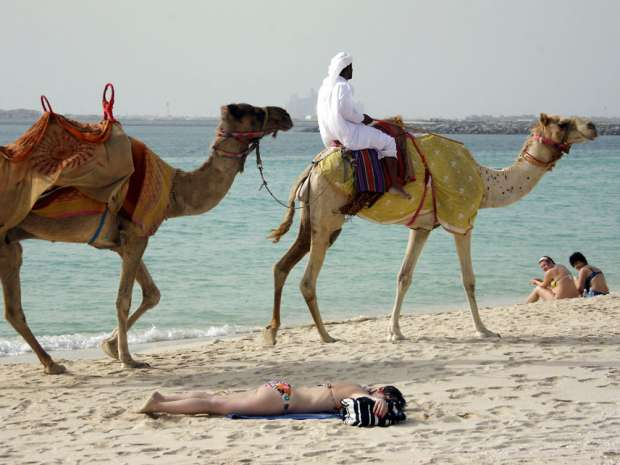 An Emirati man riding a camel passes by a foreign women sunbathing on a beach in the Gulf emirate of Dubai on ...