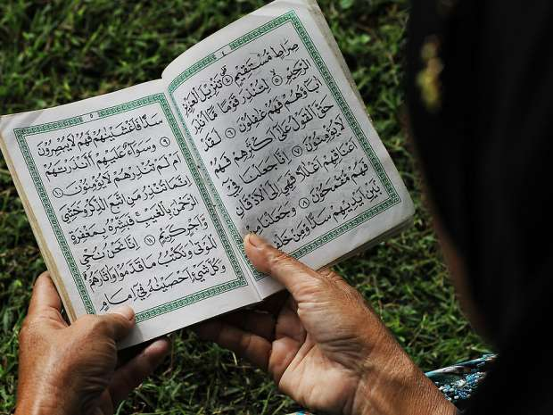 Acehnese woman holding Al-Quran when he read a prayer for friends and families of those killed by the Indian ...