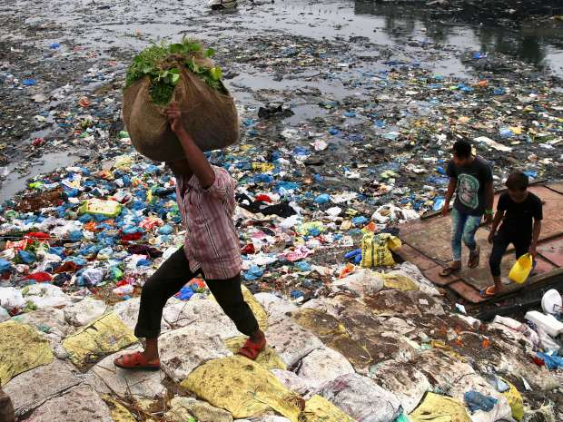 A man carries a sack of vegetables as he walks past a polluted canal littered with plastic bags and other ...