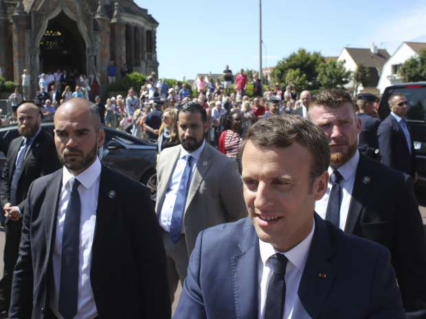 French President Emmanuel Macron, surrounded by bodyguards, leaves a polling station in Le Touquet, northern ...