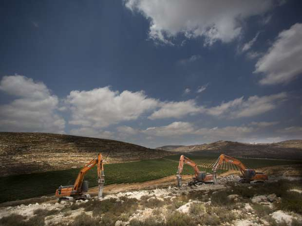 Diggers break the ground for a new settlement near the settlement of Shilo, West Bank, Wednesday, June 21, ...