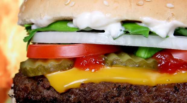 Silhouette of a cheese burger loaded with summer garden vegetables isolated on fire,