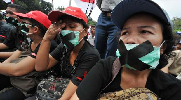 Indonesian Christians cover their mouths during a protest against attacks on churches in Jakarta on August ...