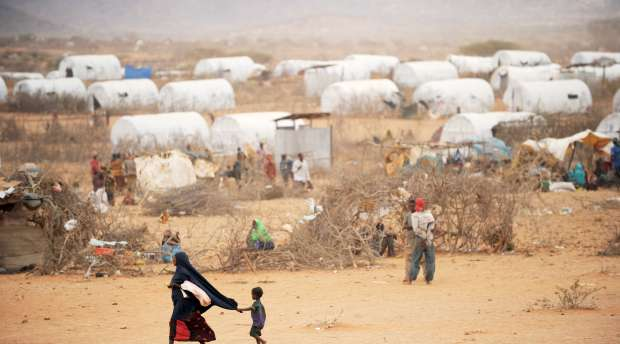 A young Somali child holds onto his mother's veil as they walk through the Kobe refugee camp near the ...