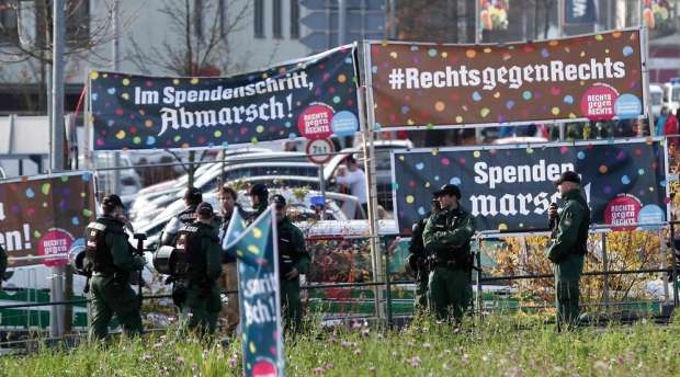 Picture taken on November 15, 2014 in Wunsiedel, southern Germany, shows policemen standing next to banners ...