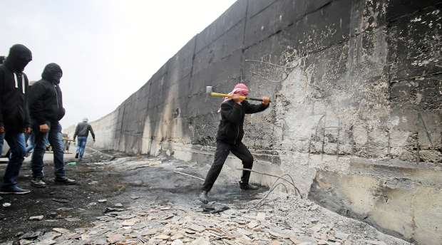 ABU DIS, EAST JERUSALEM - NOVEMBER 17, 2014 - Palestinians trying to tear down the wall in the town of Abu ...
