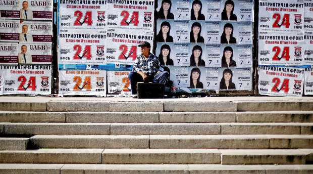 A man with a shoe shine stand waits for customers in front of election posters in Plovdiv October 1, 2014. ...