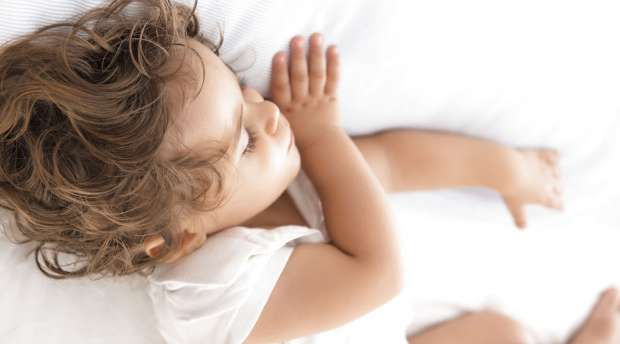 Serene and cute baby sleeping on a pillow in the