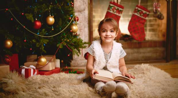 Happy girl with book looking at camera on Christmas