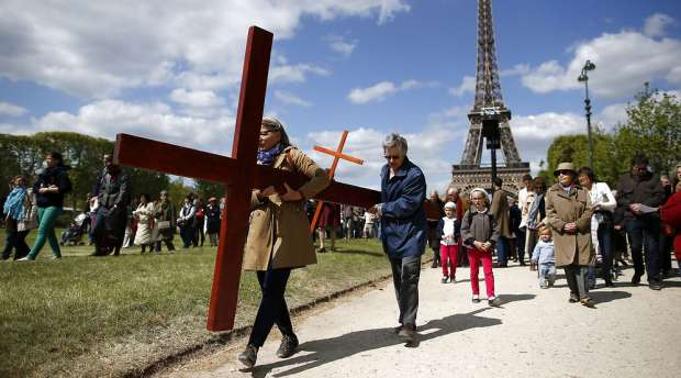 """Pilgrims attend the annual Good Friday """"Stations of the Cross"""" procession at the Champs de Mars ..."""