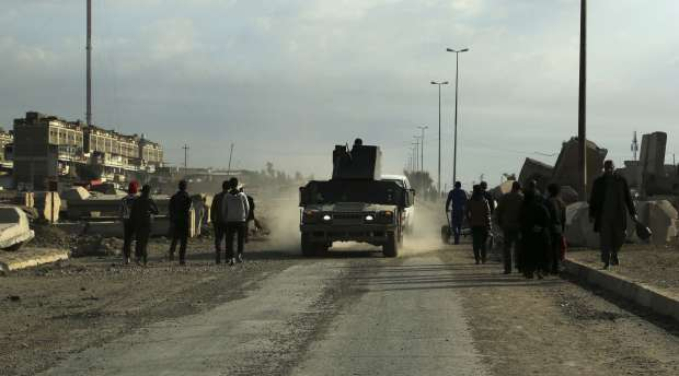 An Iraqi Army armored vehicle patrols while civilians return to their neighborhood recently liberated from ...