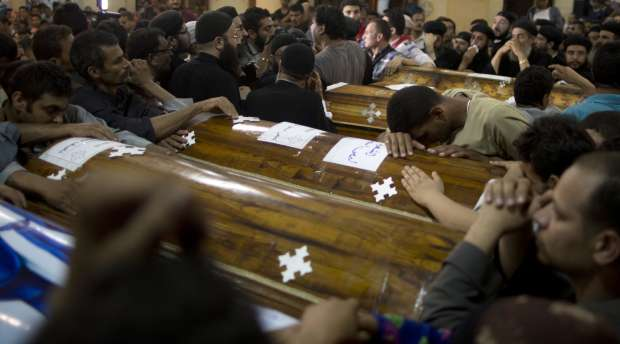 Relatives of Coptic Christians who were killed during a bus attack, mourn by their coffins during a funeral ...